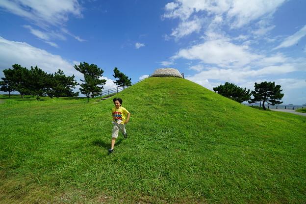 丘を駆け降りる少年