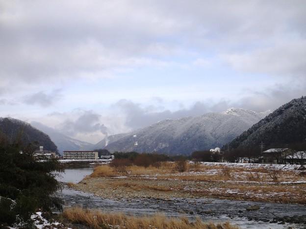 老家の煙と山の雪