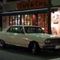 夜のカフェ前に停まる外車