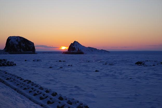 写真: 流氷の海への日没