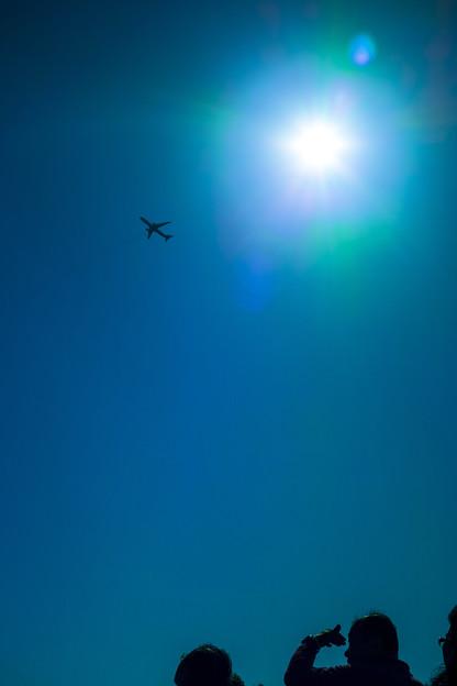 旅客機を船上から見上げる人々