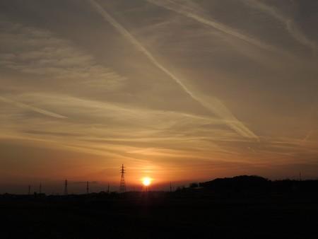 飛行機雲が錯綜する夕陽
