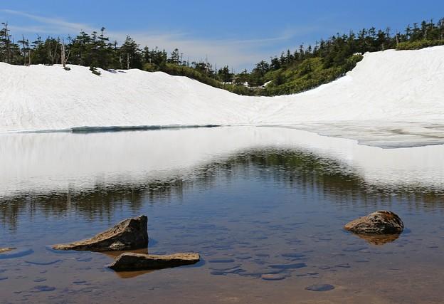 写真: 雪残る明美な湖の畔