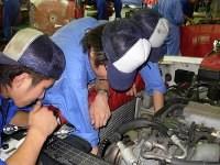 訓練生が車のエンジンルーム内を点検しています。
